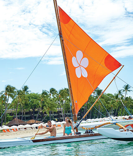 A young man and woman paddle an outrigger canoe with an orange sail featuring a white plumeria blossom design.